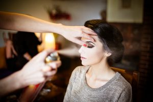 Beautiful bride doing her hair and makeup. Hairstylist spraying