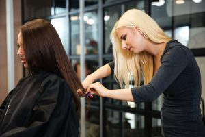 Young female hairstylist doing a haircut to a client in beauty s