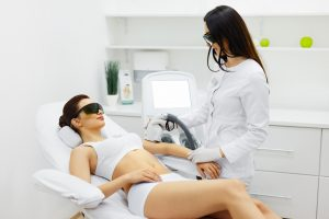 Esthetician provides hair removal services for clients.