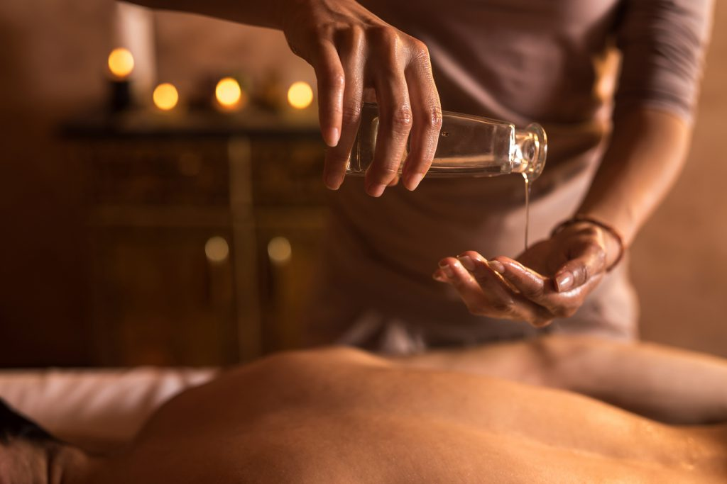 Close-up of massage therapist pouring oil in hands during massage at the spa.