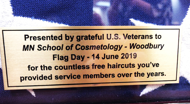 "Inscription on U.S. flag plaque reads: ""Presented by grateful U.S. Veterans to MN School of Cosmetology-Woodbury for the countless free haircuts you've provided service members over the year."""
