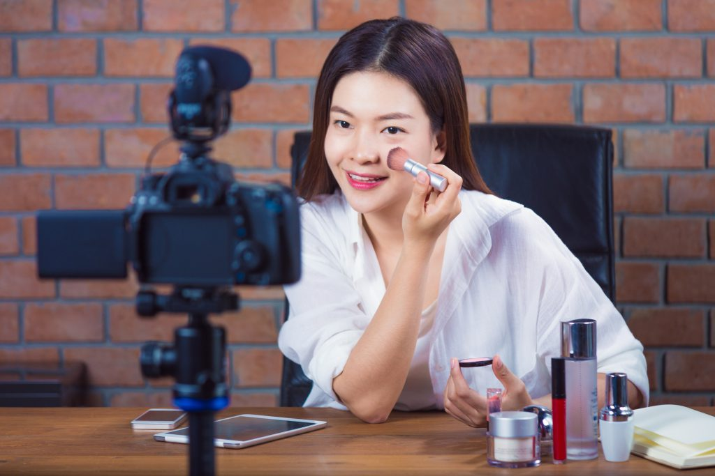 Young makeup blogger demonstrating makeup application techniques