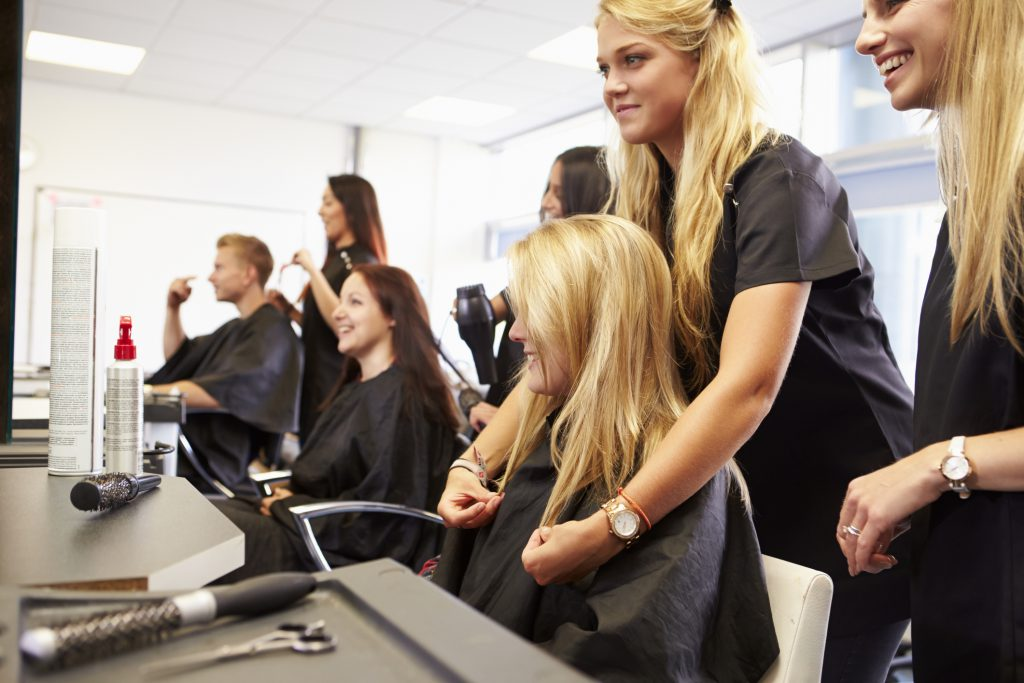 Instructor helping students in cosmetology diploma program