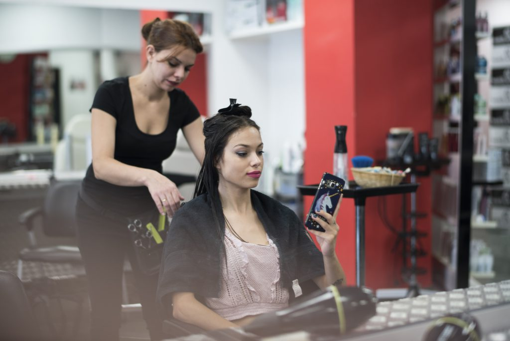 Student studying to become a cosmetologist by cutting a client's hair