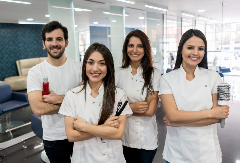 Smiling cosmetologists holding tools necessary to getting their career started