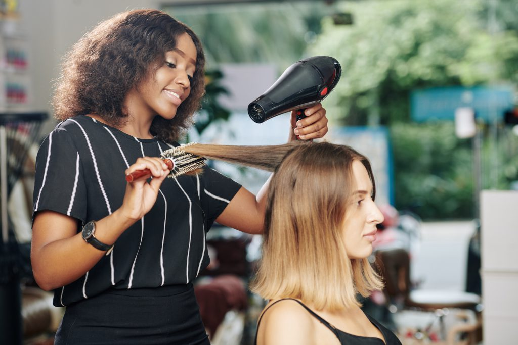 Cosmetologist performing her typical duties of drying a clients hair.