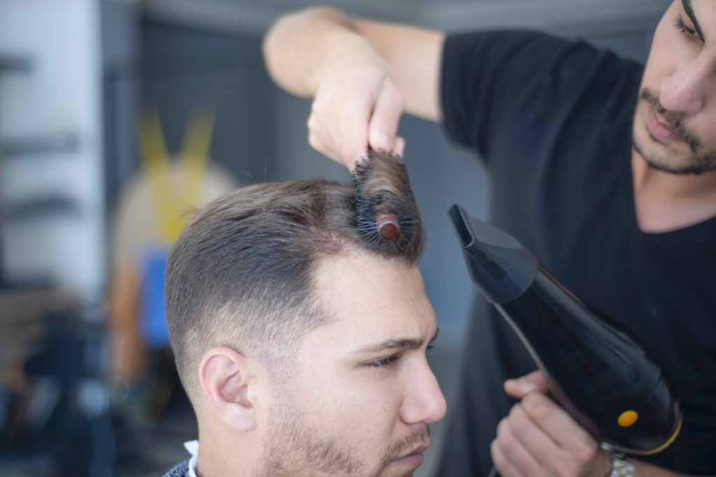 Male client at a beauty salon getting his hair designed.